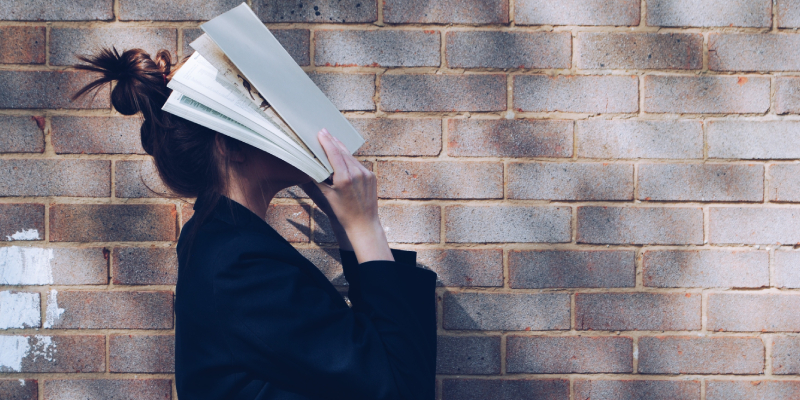A Young lady Hide Her Face With A Book About Entreprenaur In A Brick Background.