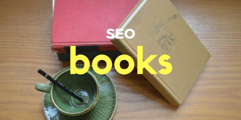 Two Books About SEO Which Is Placed On The Wooden Deck Table With A Cup And Saucer.
