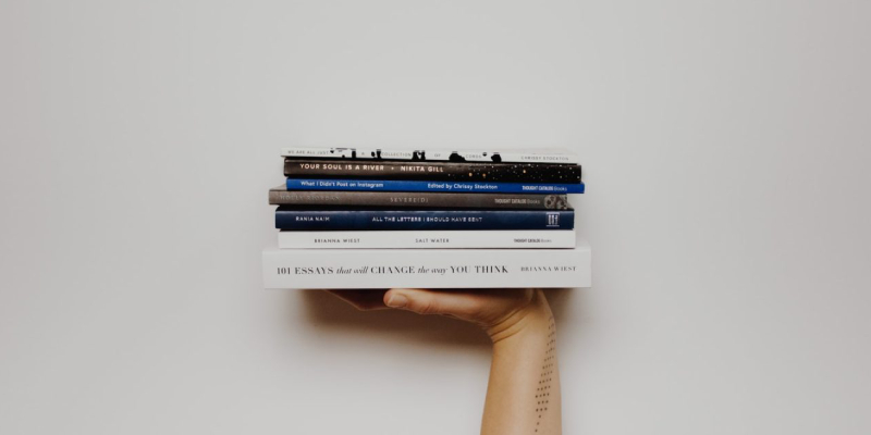 A Pile Of Books About Branding That Has Holding By A Human Hand In A White Background.