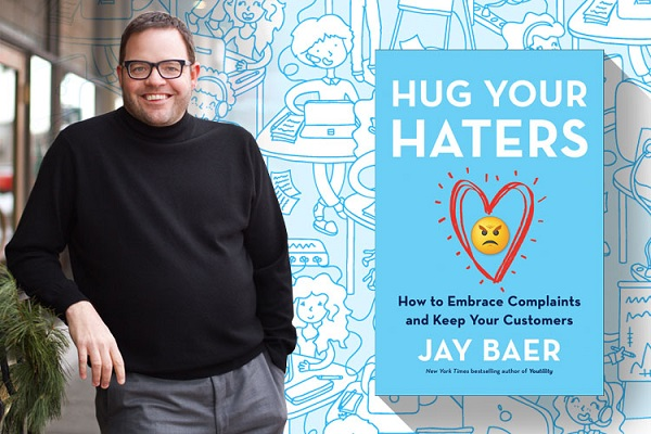 A Book About Hug Your Haters By Jay Baer On Display With An Image Of The Author.