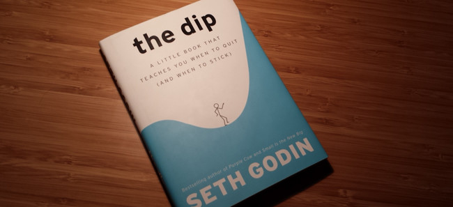 The Dip - A Book By Seth Godin Placed On The Wooden Table.