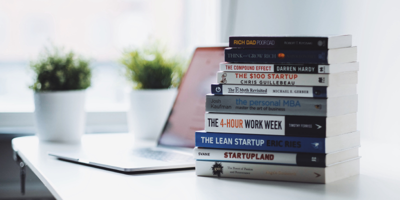 A Pile Of Books About Entrepreneurship Skills. Placed On The White Table.
