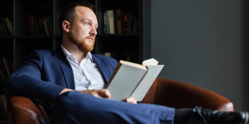 An Entrepreneur Reading A Book About Entrepreneurship Skills.