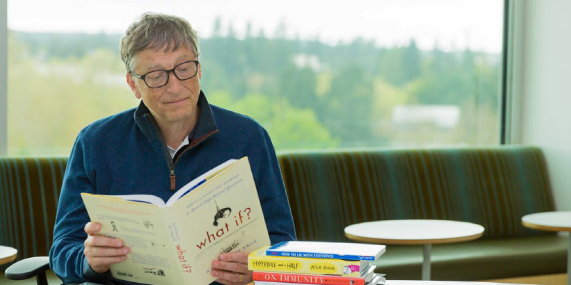 A Great Business Magnet And Philanthropist Holding And Reading A Book Called What If.