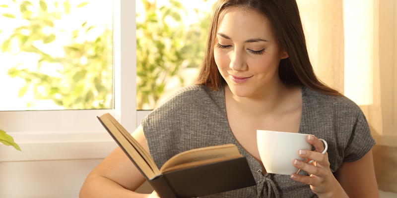 A Smiling Young Lady Reads A Book And Have A Cup of Coffee In Her Hand.
