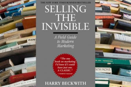 A Shelf Full of Marketing Books Infront Of A Book Selling The Invisible By Harry Beckwith.