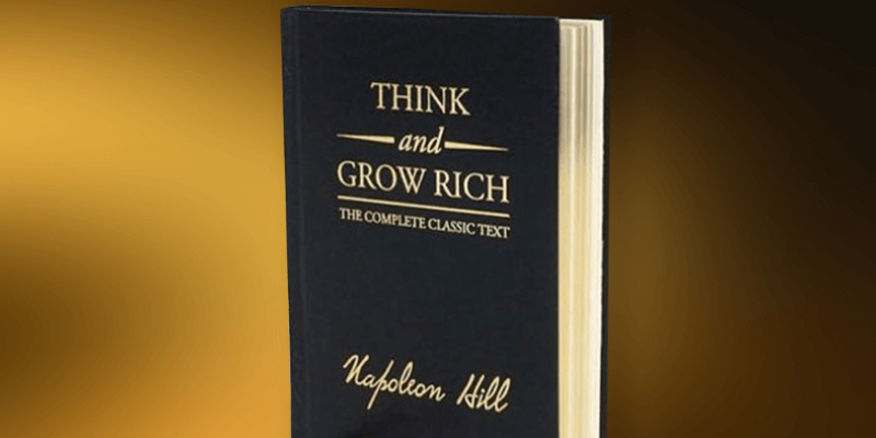 Think And Grow Rich - A Book By Napolion Hill On Display In A Brown Background.